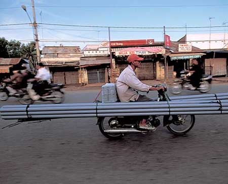 transporting pipes on a moped
